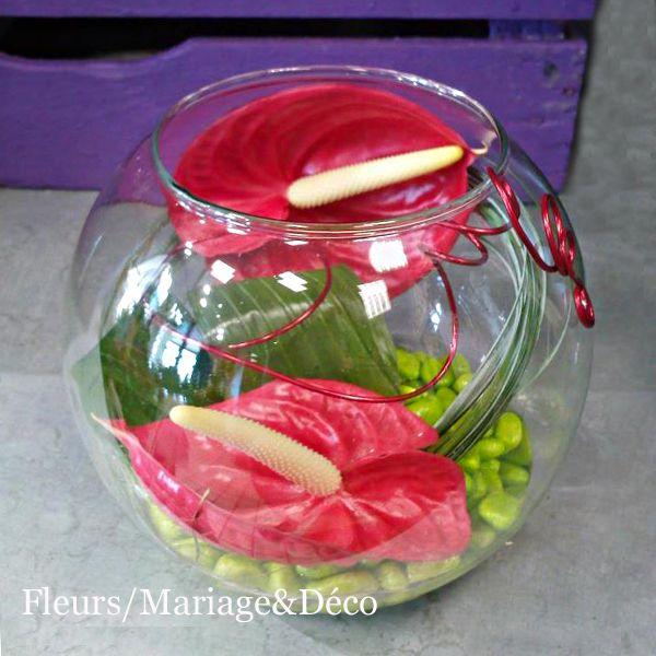 Pour une décoration de table toute en transparence,cet aquarium en verre est travaillé avec des anthuriums rouges ou blancs (l'anthurium est une fleur exotique très résistante)