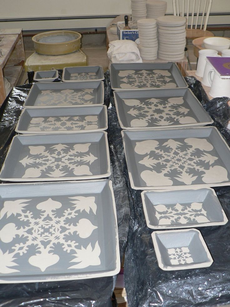 Patterns made by brushing colored slip over handmade paper stencils.  Let dry, then peel them away.