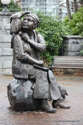 Statue of Emily Carr outside the landmark Empress Hotel Emily seen with her monkey Woo on her shoulder and her dog Billie.