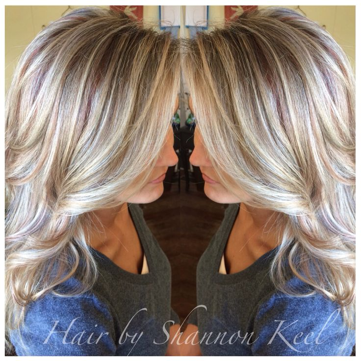 Platinum blonde Hilights and  lowlights with little pops of reds an browns. Long layers show off the pretty hilights in her hair