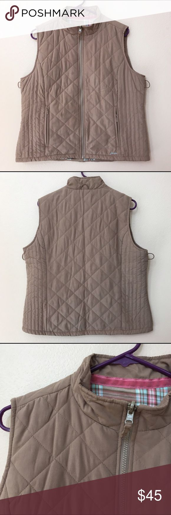 "Light brown Joules clothing quilted vest Light brown / tan quilted vest from Joule Clothing. Purchased in England. Mock neck and fully zips up the front. Two hip pockets. Three elastic loops (1 on neck, 2 on sides). Logo embroidered on the bottom. Not quite sure the material, the exterior is soft and lightweight. Interior is likely cotton. Interior is lined with plaid fabric in pink, blue, and tan. US Size 12. Measures 26.75"" neck to hem, 22"" in bust, 21.5"" in waist. Excellent condition, no…"