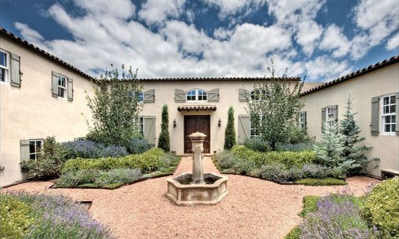 France meets the Southwest. Plantings of lavender in a front yard with a formal French garden.