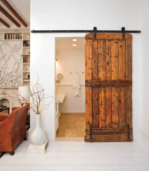 The owners of this home upgraded the old track system separating the white bathroom from the living room by installing a beautiful cast-off barn door.