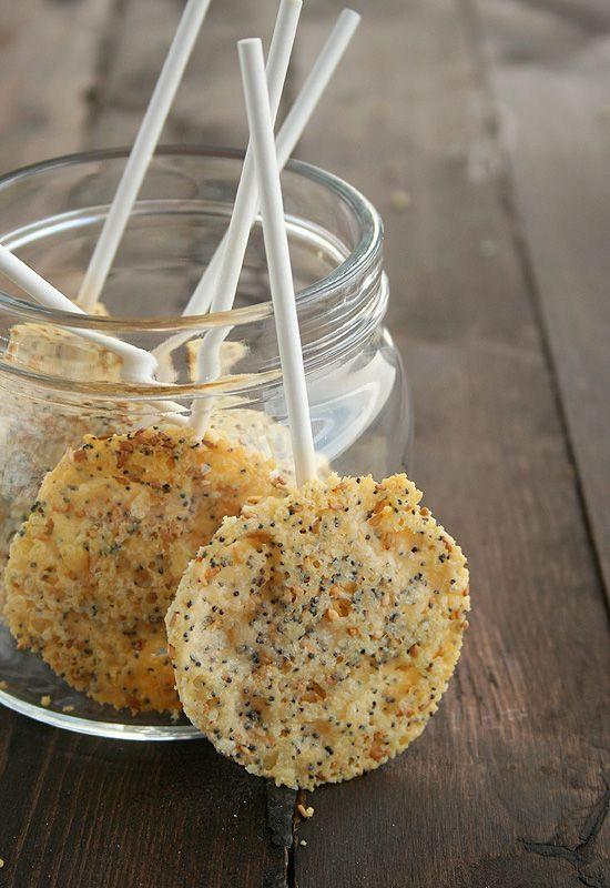 Queso en polvo o virutas- Semillas de amapola- Semillas de sésamo- Palitos de brocheta. Mezclamos en un cuenco el queso y las semillas. Forramos la bandeja  con papel vegetal. Colocamos, con ayuda de un aro o cortapastas, montoncitos de queso y semillas separados unos centímetros entre sí.En el centro de cada montón ponemos un palito o brocheta, lo tapamos con un poco de mezcla de queso y semillas. Horne 5′ enfriar 2′ en la bandeja…