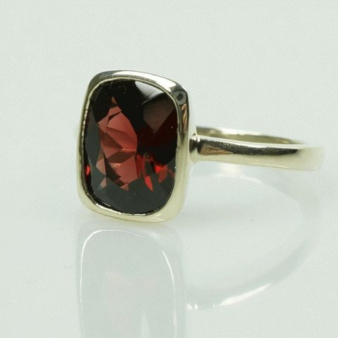 A beautiful Deep Red Almandine Garnet bezel set in 18k Green Gold.The color of this cushion cut Garnet is nicely complemented by the subtle tones of the green gold it is set in. Simple and graceful is