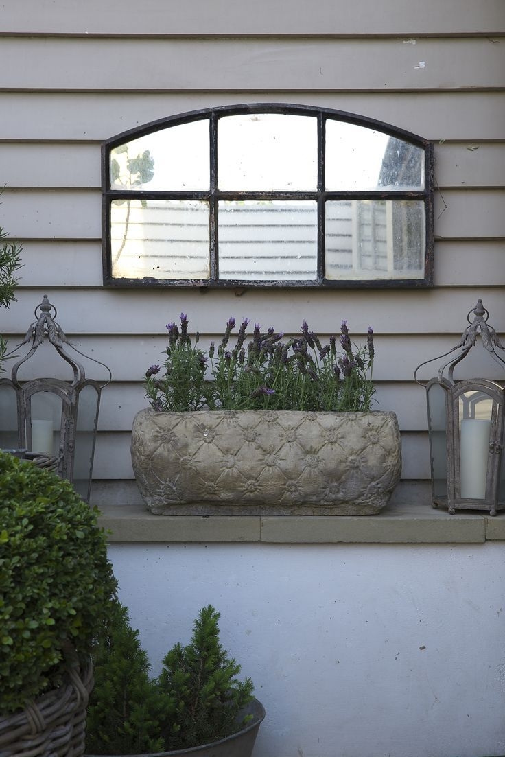 Leopoldina Haynes has used some very simple but lovely decorative touches - Here the mirror, concrete pot + beautiful lanterns sit on a shelf, which adds support to the garden beds