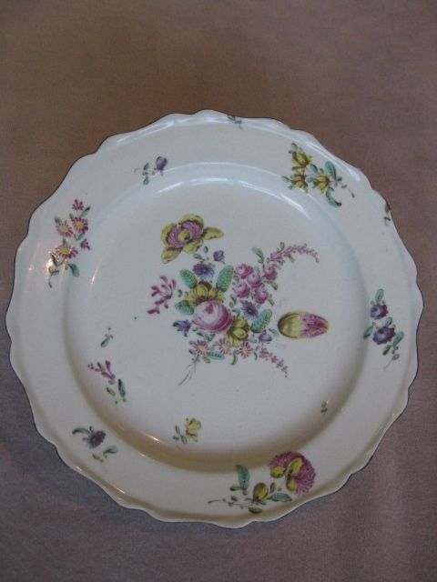 """A Bow plate painted with bouquets and sprays of puce , blue and yellow flowers within a chocolate lined wavy and shaped rim.  Unmarked    Circa  1762 Width 8 3/4"""""""