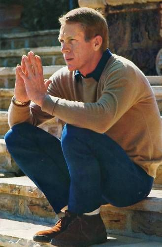 McQueen wearing a sweater, tapered pants and his brown suede Desert Boots.
