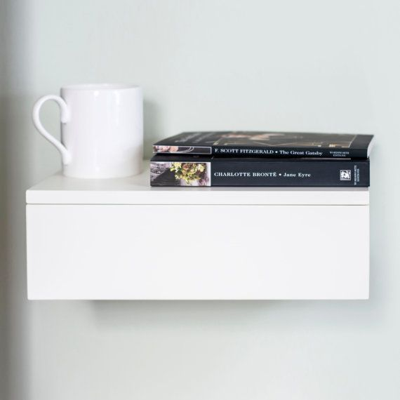 Solid beech floating bedside table in painted white. Super minimalist design for small bedrooms. Single floating drawer which attaches to the wall to maximise space. Finger grip under the drawer for easy opening. Plenty of space on the surface for all your book and lamp needs. Painted in pure white. Also available in natural beech wood.  Dimensions: L30cm x D20cm x H10cm  In stock NOW for immediate dispatch