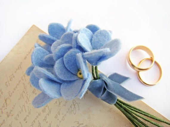 Wedding Boutonniere, Felt Forget Me Not, Lapel Pin, Felt Flower, Grooms Flower The blue Forget Me Not symbolizes faithful love and memories. What could be a more perfect choice for your grooms boutonniere? This is a cluster of seven Forget Me Nots with delicate yellow centers tied into