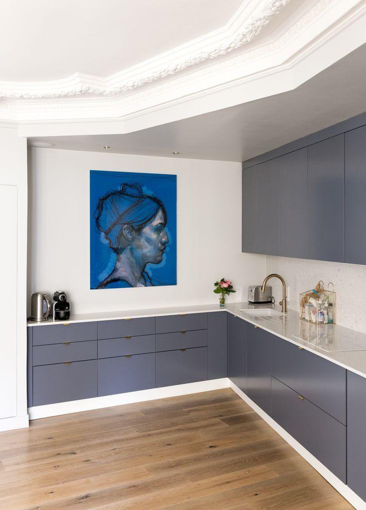 Des détails : cuisine teinte RAL qui se détache sur les moulures blanches, le marbre blanc et les plinthes blanches. Le robinet en laiton rapelle les poignées dorées.