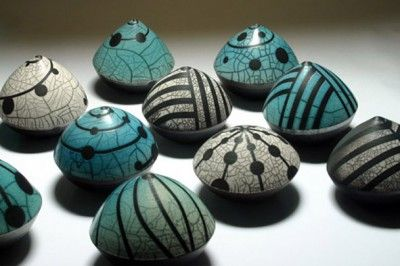 """Seedpods by Eric Moss. """"Apple-sized Ceramic Sculptures are finished with simple, bold geometric designs that he creates using a sprayed glaze over tape or paper resist patterns""""."""