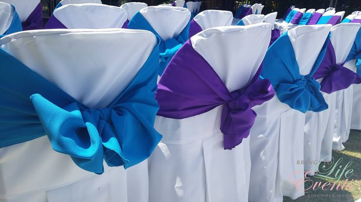 Blue & Purple tiebacks on white chair covers for wedding ceremony