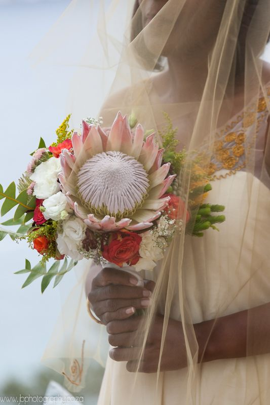 Hand tied King protea bouquet with white lisianthus and orange cherry brandy roses, golden rod and fynbos. Thanks to Jacques Bartie Photography