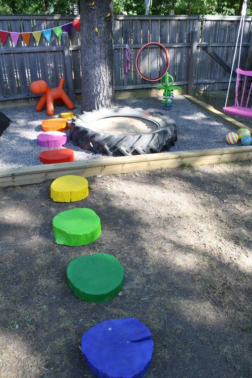 "rainbow wooden stepping ""stones,"" tire sandbox, rainbow bunting, and bright chair swing! I love it all!"