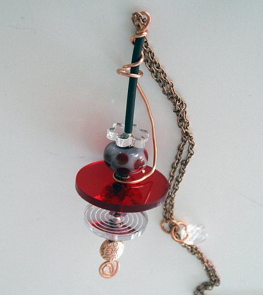 Hänge gjort av koppar, plexiglas, lampwork och gummi, hänger på en lång kopparkedja.  Pendant made of copper, plexiglass, lampwork bead and rubber, long copper chain.