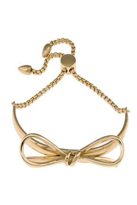 Vackert armband med en klassisk rosett i guld.Fint att bära som det är eller med ett nätt armband.  Material: Rostfritt stål med blank guldplätering. Nickelsäkert. Lås som gör storleken justerbar och enkel att ta på sig själv.