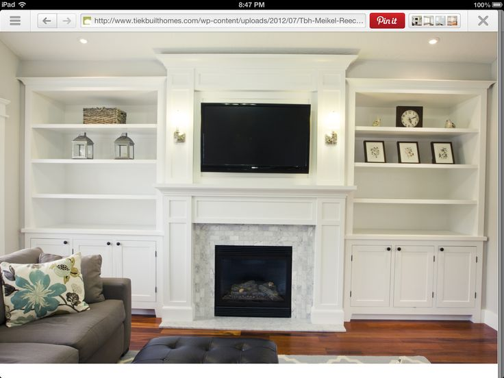 White paneled fireplace surround with tv and built in for Living room uplighting