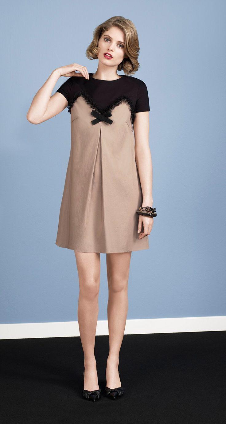 Robe trapèze bi-matière en popeline de coton stretch et haut en jersey de coton noir. Détails sur la poitrine en résille noire. Nœud noir décoratif non amovible. Fermeture zippée au dos. Longueur : 45 cm.