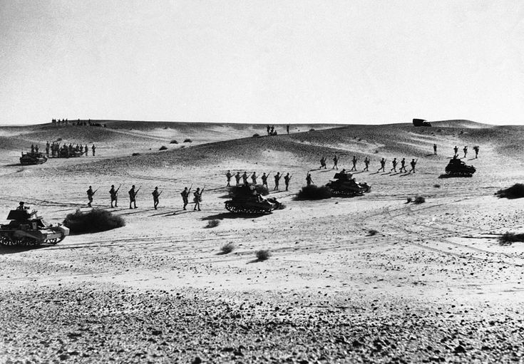 Australian troops string out behind tanks in a practice advance over North African sands, on January 3, 1941. The supporting infantry is spread out thinly as a precaution against air raids. (AP Photo)