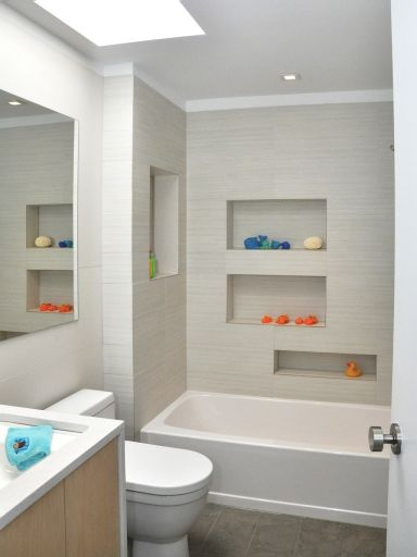 Softly-striated white porcelain tiles cover the walls while a slightly darker limestone tile accents the floor.
