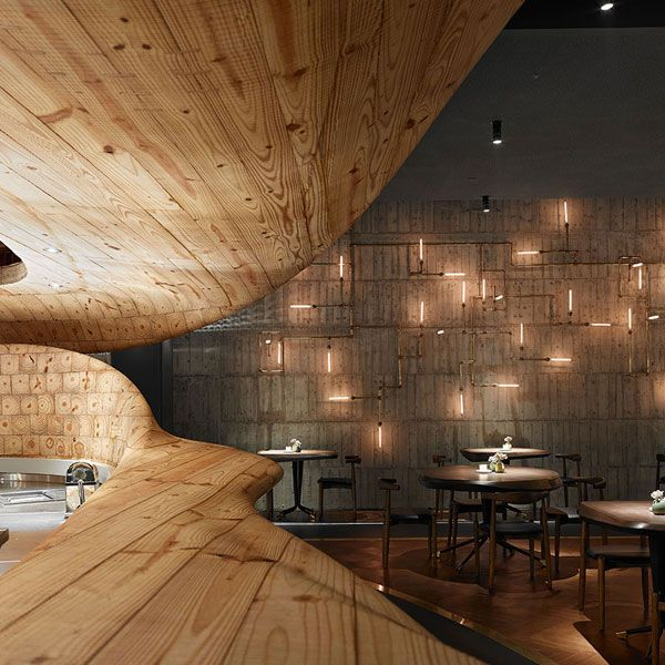 The main dining area features custom-designed tables and chairs made of Taiwanese Ash wood, cut out of wooden blocks from techniques traditionally used in ...