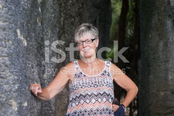 Senior Lady Rests against a rock wall. royalty-free stock photo