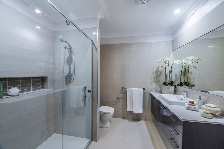 #Bathroom #style ideas from #Ausbuild's Bellfield display #home. www.ausbuild.com.au. This #Bathroom presents a clear, chic look, with a glass #shower #door and fresh white #walls. The #tiled #bathtub is an inviting shade of espresso and perfectly compliments the cupboards.