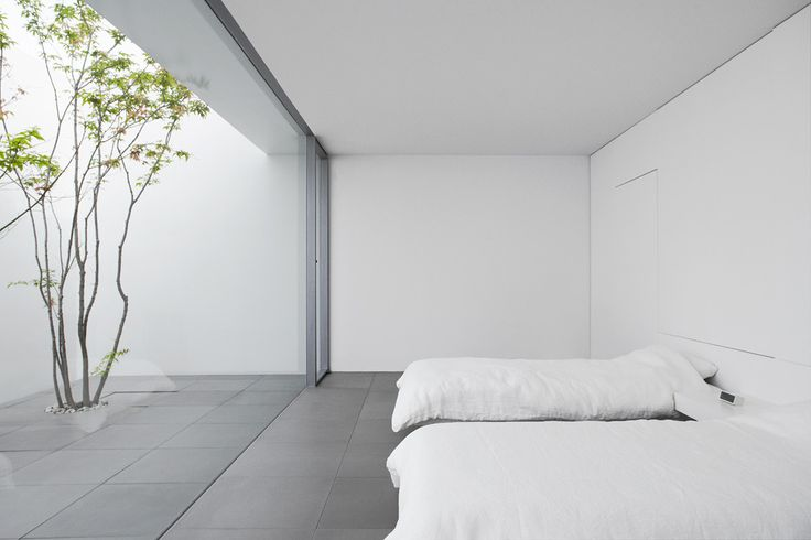 Bedroom with a view to a small patio. the Minimalist House by Shinichi Ogawa. Photo by Jonathan Savoie  Architecture.