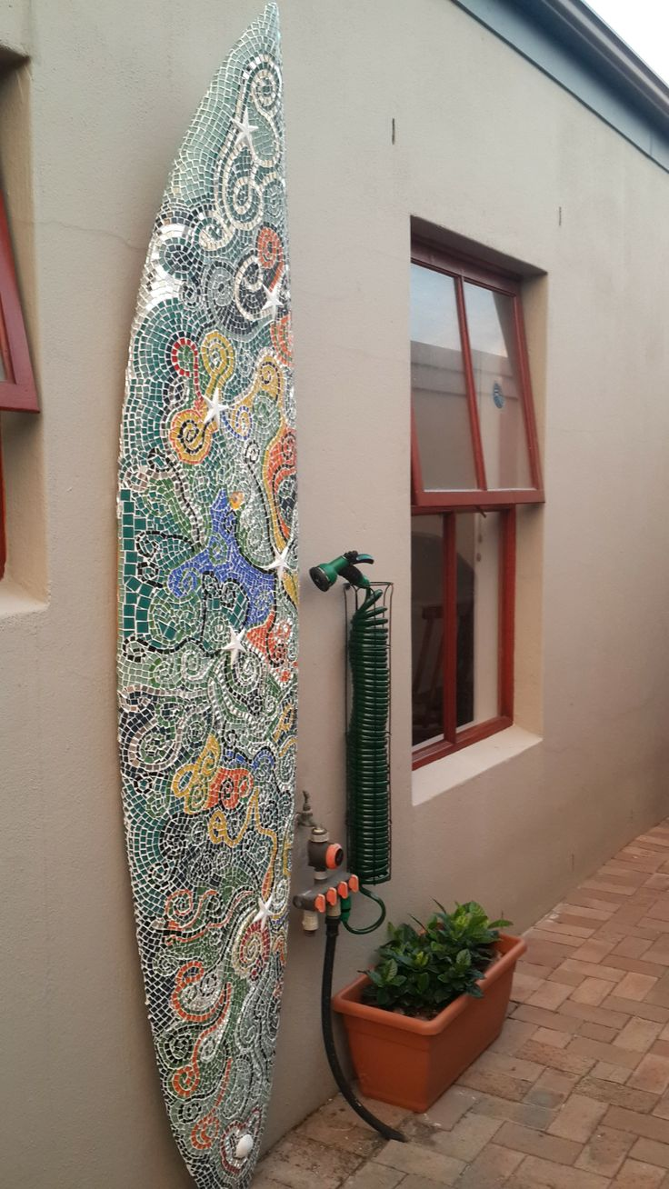 Surf board with mosaic tiles and a hose pipe with a shower head.