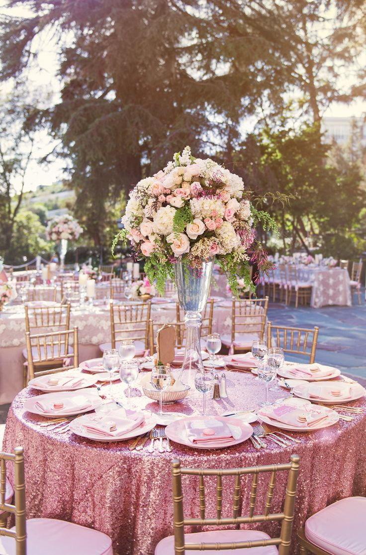 Sparkly table cloths with towering blush pink flowers for the wedding reception