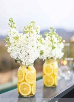 Lovely Lemon and White.  Put a thin vase inside a large mason jar.  Line the mason jar with lemons and water.  Put your flowers in the vase.  Pretty!