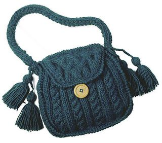 Albem is a cabled bag with knitted handle, tassels and a button closure.