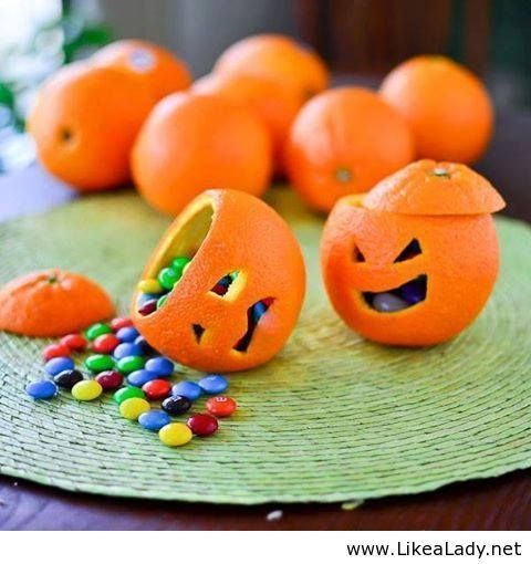 Halloween favours carved into an orange, filled with Smarties. Cute.