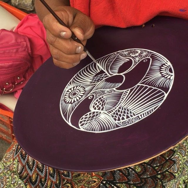 Xochitl handpainting a Clay Decorative Plate.