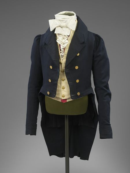The cut-away coat remained formal daywear for men until the 1850s. This example has long tight sleeves, puffed at the shoulder, a style typical of the period 1815-1820. The roll collar has an M-shape notch, introduced about 1803, and a waist seam.