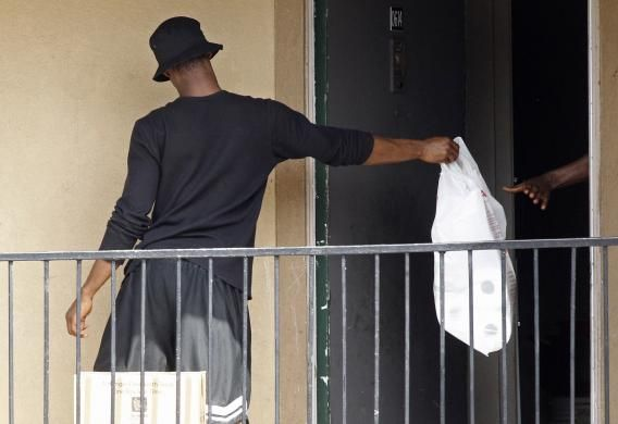 A man passes a bag, delivered by the Red Cross and the North Texas Food Bank, in to the apartment unit at The Ivy Apartments complex where a man diagnosed with the Ebola virus was staying in Dallas, Texas October 2, 2014. REUTERS-Mike Stone