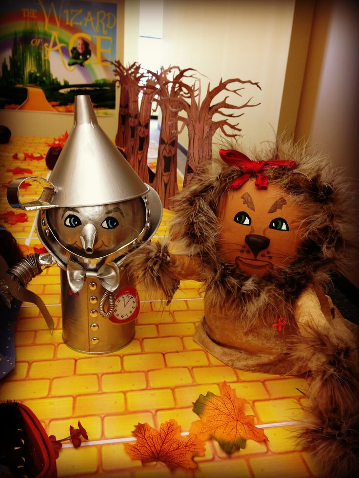 "The Tin Man and Cowardly Lion by Debra McNally.  The Tin Man standing guard is a pumpkin, tin can, funnel for his hat, top of funnel cut off and used for the nose, aluminum foil for the arms, I painted his face with acrylic paints and the best paint ever for crafting, ""Martha Stewart Silver Liquid Gilding Paint"". One coat was all it took to cover everything.  The Cowardly Lion is basically acrylic paint for the face, material scraps and a boa :)   I made these for our office Halloween…"