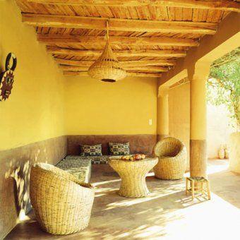 """Le salon en terrasse est bâti en """"deske"""", un ciment coloré dans la masse, et est équipé d'une table et des fauteuils en jonc tressé, d'une banquette, de l'artisanat marocain, recouverte d'un tissu imprimé africain du Togo."""