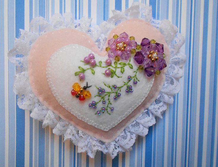 - Coração feito em feltro 10,5 cm x 8 cm e com um coração interno de 7 cm x 5,5 cm.  - Com flores feitas de bolinhas e losangos de acrílicos, bolinhas douradas, pérolas, miçangas. <br>- Bordado e com renda. - Borboleta feita de miçangas e losangos de acrílicos. - Pode ser usado como chaveiro, móbile, enfeite de Natal, enfeite de porta, enfeite para carro, guirlanda. - Felt heart with flowers and butterfly.