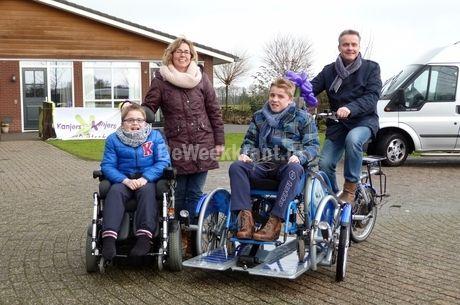 Bram, moeder Heidi, Thomas en vader Jan met de nieuwe rolstoeltransportfiets met trapondersteuning.