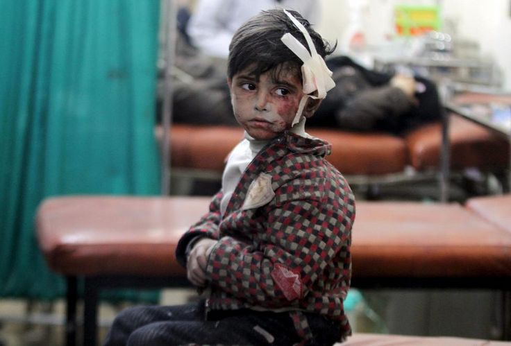 An injured boy waits inside a field hospital after what activists said were…