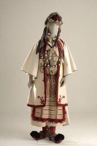 Γυναικεία ενδυμασία νομάδων Πίνδου  Νυφική ενδυμασία Νομάδων Πίνδου. Η ενδυμασία φοριόταν από τους Αρβανιτό- βλαχους που ονομάζονταν Καραγκούνηδες της Ηπείρου. Αποτελείται από λευκό πουκάμισο με κέντημα στον ποδόγυρο και την τραχηλιά, μαύρο σεγκούνι και υφαντή ποδιά. Στο κεφάλι φορούν πρόσθετες κοτσίδες ενώ ο κεφαλόδεσμος αποτελείται από ψηλό κωνοειδές καπέλο που τη βάση του περιτρέχει ασημένιο έλασμα, ως διάδημα. Οι ασημένιες αλυσίδες στο στήθος, η ζώνη με την πόρπη, το κεμέρι, και τα…