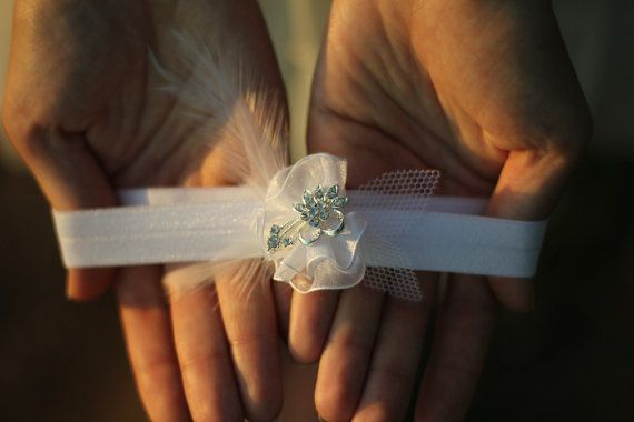 This bridal garter is adorned with a beautiful crystal rhinestone flower. I created the white flower using white chiffon ribbons with soft feather