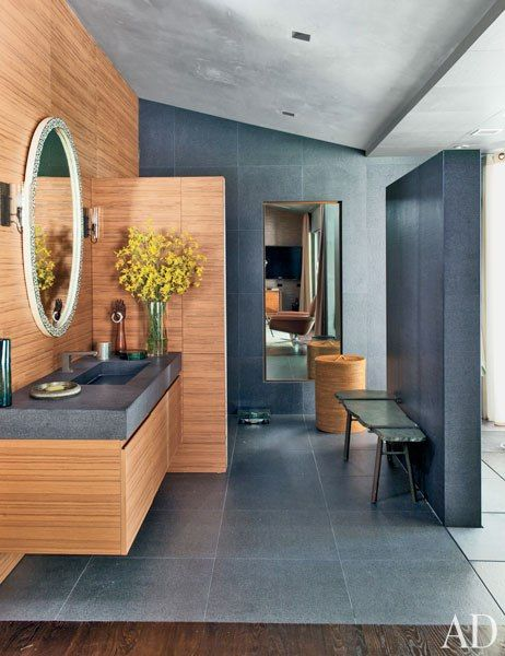 JOHN LEGEND and wife Christine Teigen Hollywood Hills House.  The master bathroom features Claro 2 wall sconces by BOWLES and LINARES www.bowlesandlinares.co.uk Laurameroni cabinetry of rift-cut teak, an antique stone-top bench from Inner Gardens, and a Waterworks hamper.