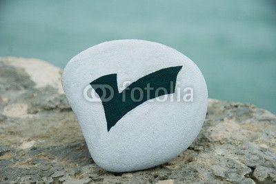 check mark symbol on a stone