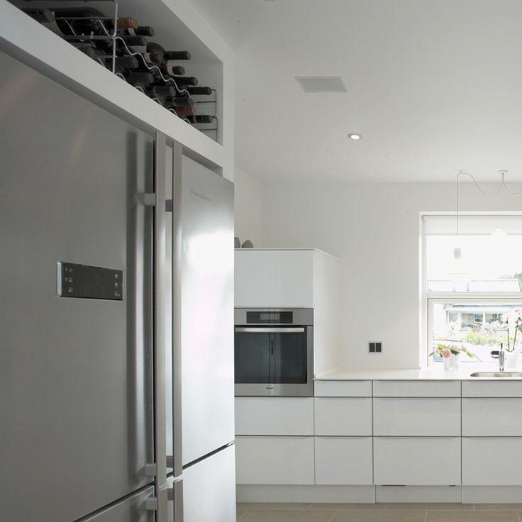 Dobbelt køle- og fryseskab i køkkenet med plads til vinreolerne foroven. Detalje med funktion.