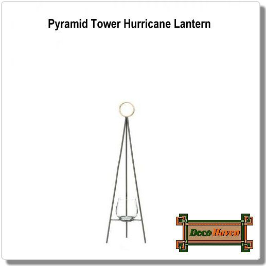 Pyramid Tower Hurricane Lantern - Sleek, slim and stunning! This minimalist hurricane lantern will glow with the light of your favorite candle while looking like a modern piece of art. Three slender legs are topped with a golden circle and the glass candle cup below is the perfect finishing touch.