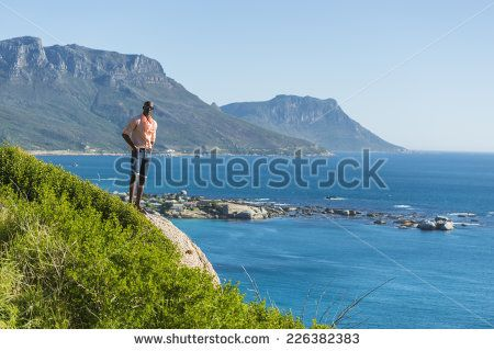 http://www.shutterstock.com/pic-226382383/stock-photo-african-black-man-standing-on-a-high-rock-overlooking-cape-town-as-he-points-and-scouts-the-blue.html?src=WuffEuvvGWj02MQSGcnIHQ-1-16 African Black Man, Standing On A High Rock Overlooking Cape Town As He Points And Scouts The Blue Sky, Ocean And Mountains On A Sunny Summers Day Stock Photo 226382383 : Shutterstock