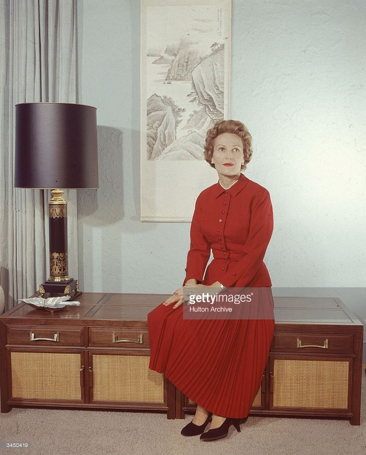 Portrait of former First Lady Pat Nixon - , wife of American President Richard Nixon, wearing a red dress and sitting on a cabinet, circa